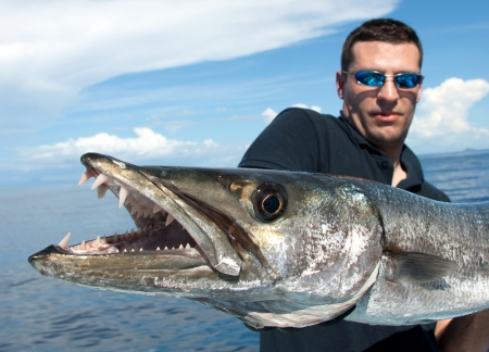 barca da pesca: Pescatore in possesso di un barracuda gigante Archivio Fotografico