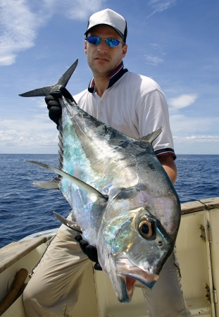 big game fishing - Happy  fisherman holding a trevally jack Stock Photo
