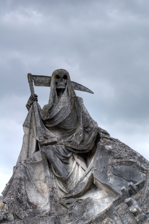 Death personified as a skeleton with a cloak and scythe photo