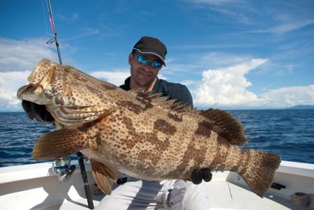 幸せな漁師、ハタを保持