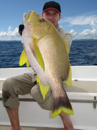 Happy  fisherman holding a beautiful yellow snapper