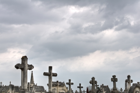 Old crosses in a cemetery with a cloudy sky