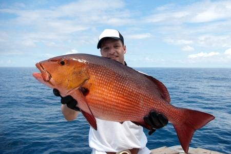 horgász: Boldog halász kezében egy gyönyörű vörös sügér Stock fotó