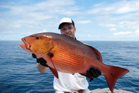 happy  fisherman holding a beautiful red snapper Standard-Bild