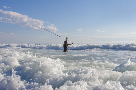 Surf fishing - Fisherman into the waves Stock Photo - 15828609