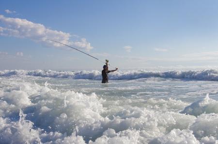 Surf Pêche - Pêcheur dans les vagues Banque d'images - 15828609