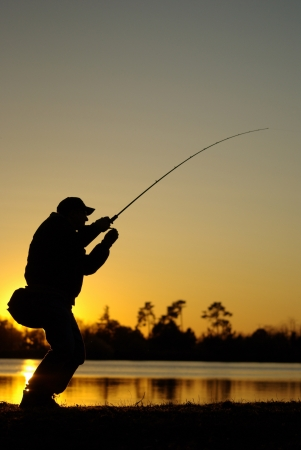 A fisherman fight against a fish at sunset