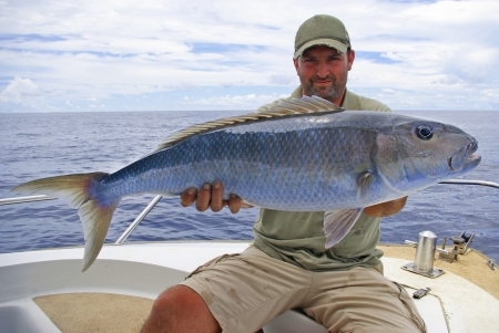 big game fishing: Lucky  fisherman holding a beautiful jobfish