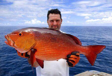 美しい鯛を持ってラッキー漁師