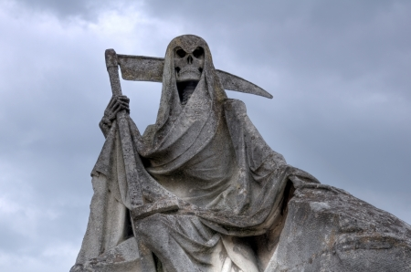 grim reaper: Grim reaper. This picture of weathered sculpture was taken in a French cemetery. This tombstone was built in memory of a sailer  Stock Photo