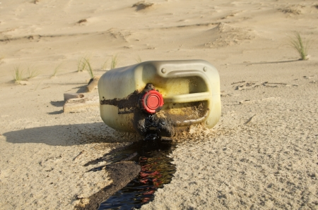 Spilled oil can on a beach photo