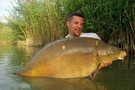 freshwater fishing: Carp fishing scene  fisherman holding a large carp