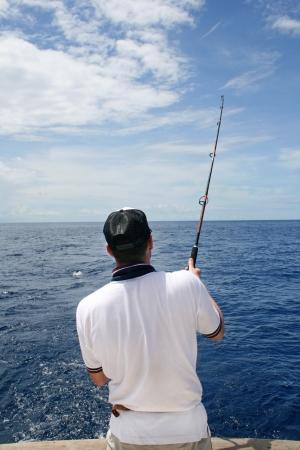 Pêche au gros Un pêcheur dans un bateau lutte contre un poisson Banque d'images - 17799326
