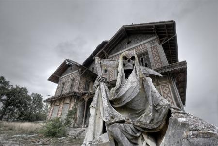 tumbas: Casa encantada abandonada y arruinada mansi�n con una estatua Gream segador en primer plano
