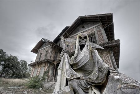 Haunted house  Abandoned and ruined manor with a gream reaper statue in foreground