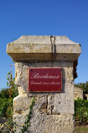 Street sign  grand crus classes, with wine in background  Bordeaux, Gironde, France Editorial