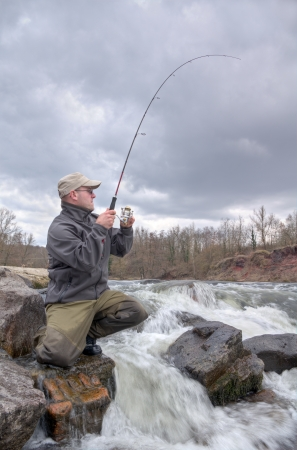 anglers: A fisherman fight against a trout in a deep river