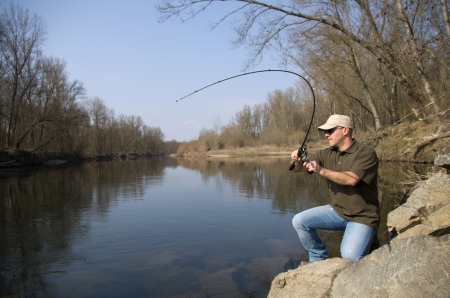 A fisherman fight against a pike in a deep river
