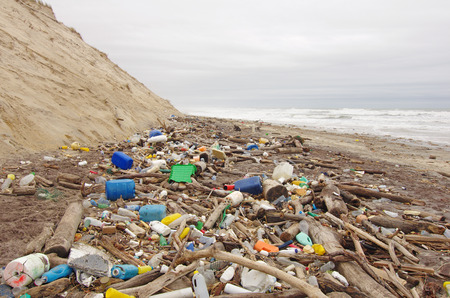 coastal erosion: garbages, plastic, and wastes on the beach after winter storms Stock Photo