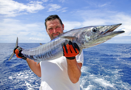 fishing scene  fisherman holding a big wahoo fish