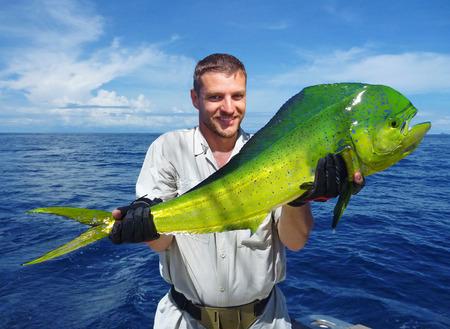 delfin: Wędkarstwo morskie, połów ryb, rybak trzyma ogromny delfina
