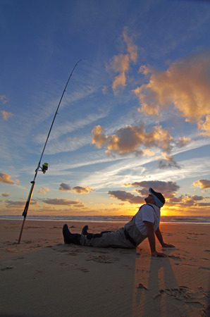 pêcheur assis sur la plage, attendant le poisson au coucher du soleil Banque d'images