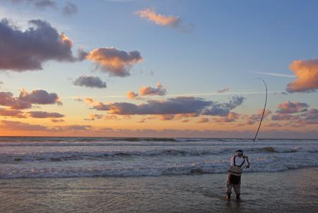 Pêcheur de surf combattant un poisson au coucher du soleil. Pêche en mer, prise de poisson, pêche de nuit Banque d'images