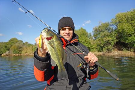 Glücklicher Fischer, der einen Bassfisch hält Süßwasserfischen, Köderfischen, Bootsangeln