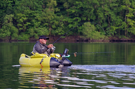 Fishing with a float tube A fisherman sitting in a comfortable float tube fight against a pike
