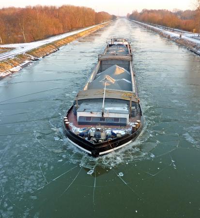 Una barcaza que transporta material navegando por un pequeño canal congelado Foto de archivo