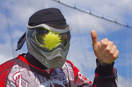 Paintball sport player with splatter on his mask