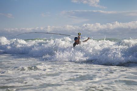 Pescador de surf en las olas. Pesca de surf casting