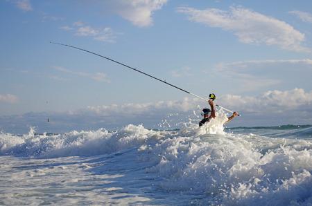 Surfen Sie Fischer in die Wellen. Angeln mit Surfcasting