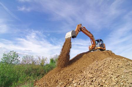 Escavatore in azione durante i lavori di movimento terra. Scarico