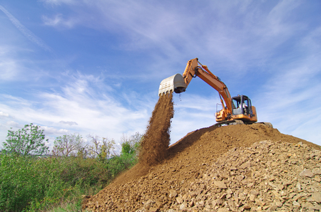 Excavator machine in action during earth moving works. Unloading
