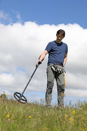 A man searching for buried treasure, ancient coins and historic artefacts with metal detector