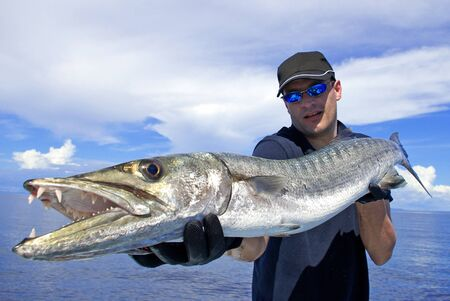 Deep sea fishing, Catch of fish, big game fishing, Lucky  fisherman holding a giant barracuda