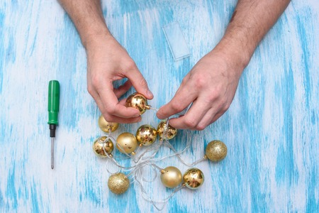 On a turquoise table a man with a screwdriver repairs a garland of gold balls.