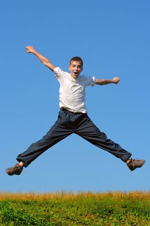 Happy and winning boy jumping on the blue sky background photo