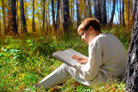 reading boy sit in autumn forest with a book Stock Photo
