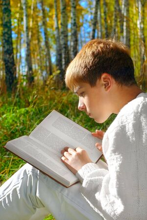 reading boy sit in autumn forest with a book photo