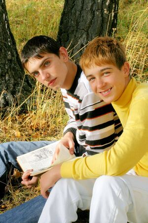 boys sitting with a book in the autumn forest photo