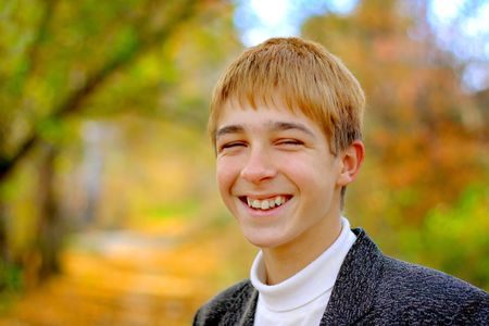 smiling teenager stand in autumn park photo