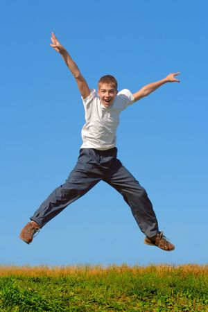 Happy and winning boy jumping on the blue sky background Stock Photo - 2135389