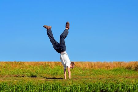 breakin: Somersault on grass on the blue sky background Stock Photo