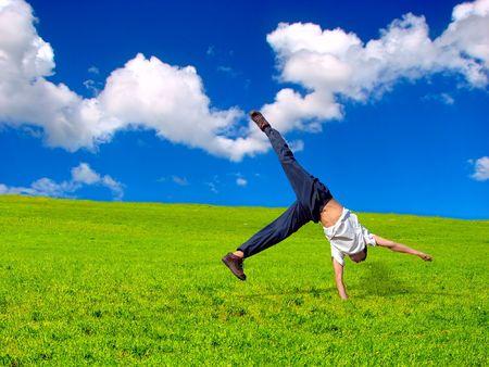 Somersault sur l'herbe sur le fond de ciel bleu