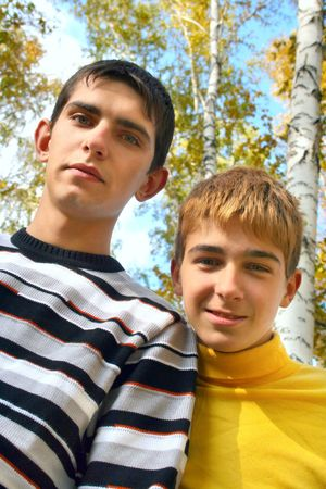 two teenagers stand in autumn forest photo