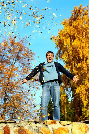 happy teenager scatter leafs in the autumn park Stock Photo - 3830215