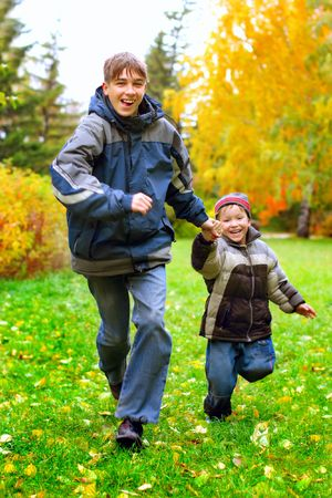 happy boys runing in the autumn park photo