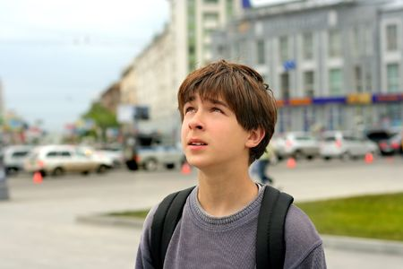 boy looks aside with attention on the street photo